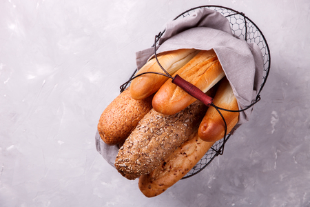 Baguettes. Mixed breads  in a metal basket on a light background.