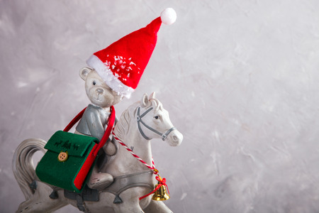 Christmas toy bear on a horse in the snow.New Year Card.Vintage style. Copy space. selective focus.