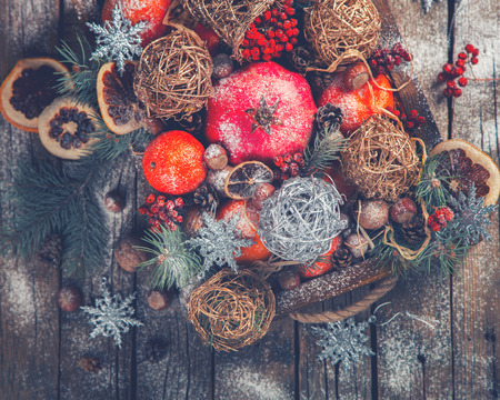 mountain ash: Christmas Toys,Tangerines,Nuts,Pomegranate,Cranberry,mountain Ash,Citrus,Berries in a wooden box.Festive Background.New Year Christmas card. Drawn Snowfall.selective focus.