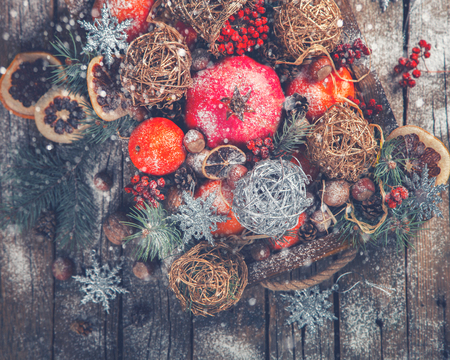 mountain cranberry: Christmas Toys,Tangerines,Nuts,Pomegranate,Cranberry,mountain Ash,Citrus,Berries in a wooden box.Festive Background.New Year Christmas card. Drawn Snowfall.selective focus.