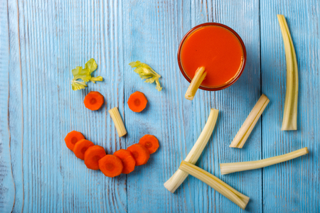 Freshly squeezed Carrot and celery juice in glass, on wooden background. Healthy food or diet concept.
