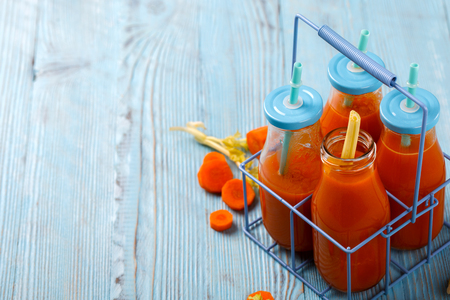 Freshly squeezed Carrot and celery juice in glass  on wooden background. Healthy food or diet concept. Zdjęcie Seryjne