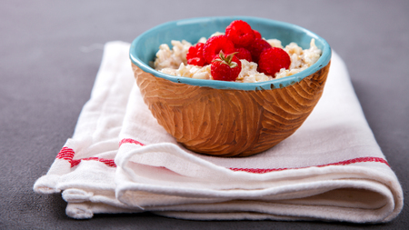 Oatmeal Porridge with fresh Berries,Raspberry.Breakfast.Concept of Healthy Eating. Copy space.selective focus. Stock Photo