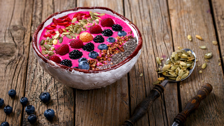 Berry Smoothie in the  bowl on a wooden Vintage Background.Detox. Breakfast Pudding topped with goji berries,raspberry, blackberry,blueberries, pumpkin, sunflower and chia seeds.Concept of Healthy Food.Copy space. selective focus.