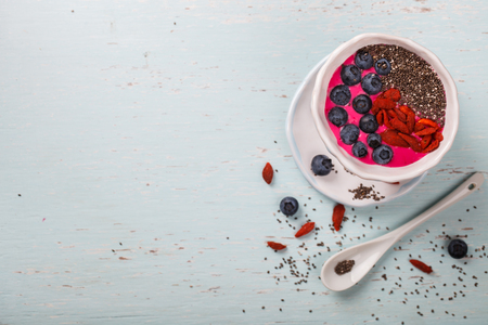 Berry Smoothie in the  bowl.Detox. Breakfast Pudding topped with goji berries, blueberries,  and chia seeds.Concept of Healthy Food.Copy space. selective focus.