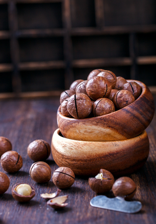 Macadamia Nut in Shell on Wooden Background.Vegetarian.Concept of Healthy Food. selective focus. Stock Photo