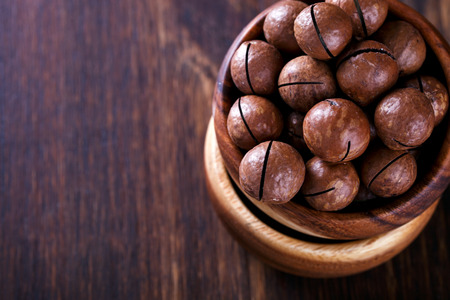 Macadamia Nut in Shell on Wooden Background.Vegetarian.Concept of Healthy Food.Copy space for Text.selective focus. Stock Photo