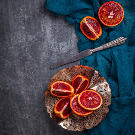 Blood Orange in a metal Plate with a knife on a dark Background.Vintage style.Food or Healthy diet concept.Vegetarian.Copy space for Text. selective focus. Stock Photo