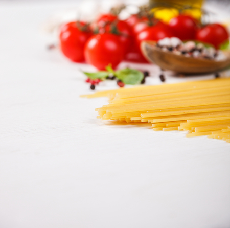Pasta Spaghetti with ingredients for cooking pasta on a white background.Copy space for Text. selective focus. Stock Photo