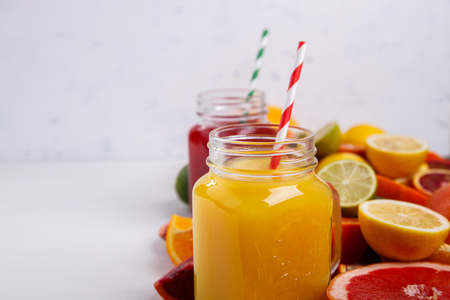 Juices Fresh Orange and Citrus on a White Background.Healthy Beverage.Food or Healthy diet concept.Mixed Colorful Tropical Background.Copy space for Text. selective focus