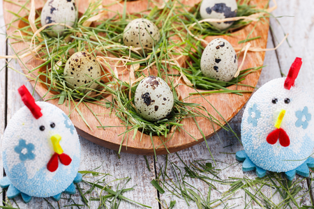 quail: Easter decorations. Quail eggs in the nest and the grass on a wooden stand.