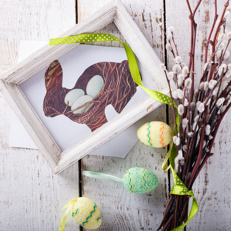 huevos de codorniz: Quail eggs and willow,the picture of the rabbit in wooden frame,Easter symbol on a light background.selective focus.