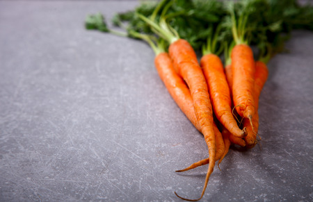 Bunch of fresh carrots with green leaves on a grey stone background. Top view. Vegetable.Food or Healthy diet concept.Vegetarian.Copy space for Text. selective focus.