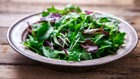 Fresh Green Mix Salad on Vintage Wooden background in a metal bowl.Leaves Of Spinach,Arugula,Romaine,Lettuce.Concept of Healthy Food.Copy space for Text. selective focus. Stock Photo