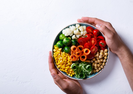 Raw mixed Vegetables and chickpeas on a white. Background Vegetarian Buddha Bowl in the Mens Hands. Food or Healthy diet Concept.Super Food.Copy space for Text. selective focus.