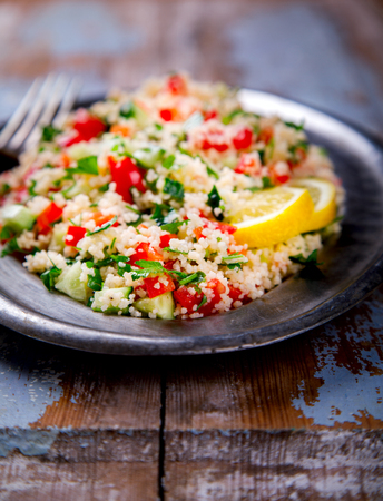 Tabbouleh salad with couscous on the plate.Traditional middle eastern or arab dish.Vegetarian.Parsley,pepper,cucumber,tomato,lemon.Middle eastern meze.Food or Healthy diet concept.Copy space for Text. Stock Photo