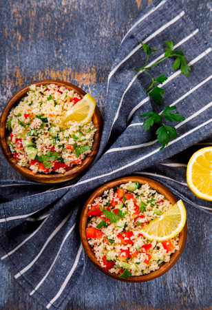 Tabbouleh salad with couscous on the plate.Traditional middle eastern or arab dish.Vegetarian.Parsley,pepper,cucumber,tomato,lemon.Middle eastern meze.Food or Healthy diet concept.Copy space for Text. 写真素材