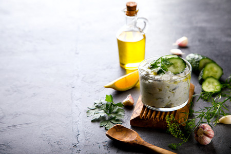 dipping: Tzatziki Traditional Greek sauce with ingredients cucumber, garlic, parsley, lemon, mint. Food Background.Snack, Meze in a glass cup.Copy space for Text.selective focus.