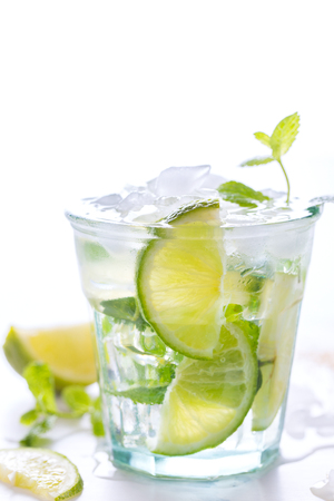 icecubes: Mojito Cocktail.Mint, lime, ice, cane sugar ingredients for making  on a white background.Cold Drink.Top View.Copy space for Text.selective focus.