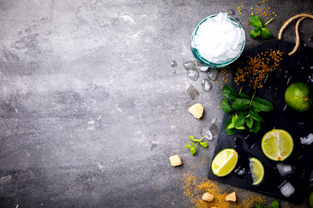 Ingredients for making Mojito Cocktail on a slate board.Mint, lime, cane sugar, ice.Cold Drink .Copy space for Text.selective focus.