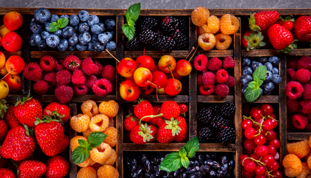 Various fresh summer Berries on the Gray Background. Mix in vintage wooden box .Raspberry, Strawberry, Blackberry, Blueberry, Honeysuckle and Green Mint.Food or Healthy diet concept.Super Food.Vegetarian.Top View.selective focus. Stock Photo