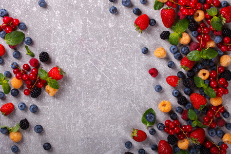 Various fresh summer Berries on the Gray Background. Mix Berries.Raspberry, Strawberry, Blackberry, Blueberry, Honeysuckle and Green Mint.Food or Healthy diet concept.Super Food.Vegetarian.Top View.Copy space for Text.selective focus.