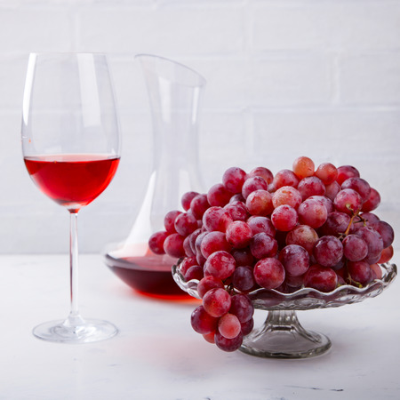 Wine Pink and Grape bunch. Alcoholic drink in a glass glass on a light background.Copy space for Text.  selective focus.