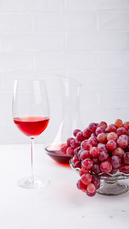 Wine Pink and Grape bunch. Alcoholic drink in a glass glass on a light background.Copy space for Text. selective focus. Stock Photo