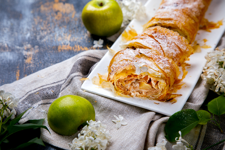 Strudel Apple and sugar powder. Biscuit from the puffed Test on the Gray Background. Dessert with Fruits.Copy space for Text. selective focus.