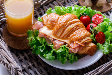 Fresh Croissant Sandwich with  Ham, Cheese,Cherry tomatoes and Salad leaf  on the Tray with Coffee  Milk and a glass of Orange Juice Breakfast in bed Delicious Baking