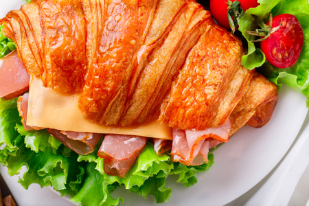 Fresh Croissant Sandwich with  Ham, Cheese,Cherry tomatoes and Salad leaf  on the Tray with  a glass of Juice Orange  Breakfast in bed Delicious Baking  Light Meal