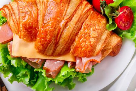 Sándwich de croissant fresco con jamón, queso, tomates cherry y hojas de ensalada en la bandeja con un vaso de jugo Desayuno de naranja en la cama Deliciosa comida ligera para hornear Foto de archivo - 87094705