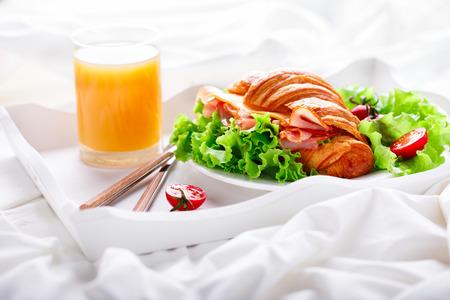Sándwich de croissant fresco con jamón, queso, tomates cherry y hojas de ensalada en la bandeja con un vaso de jugo Desayuno de naranja en la cama Deliciosa comida ligera para hornear Foto de archivo - 87299035