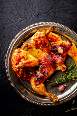 Grilled fried roast Chicken Tabaka with thyme and garlic, in Frying pan on wooden Background.Festive dish.