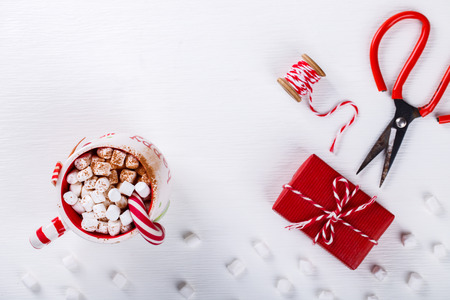 Christmas Background with Decorations and gift Boxes Cup of Festive Drink with marshmallow on a White Background  Top view. Copy space.selective focus .