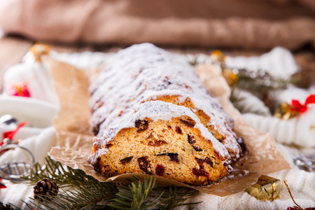 Dresdner Stollen is a Traditional German Cake with raisins on a light knitted background.Gift for Christmas.Vintage style.Fruit cake for the Holiday.