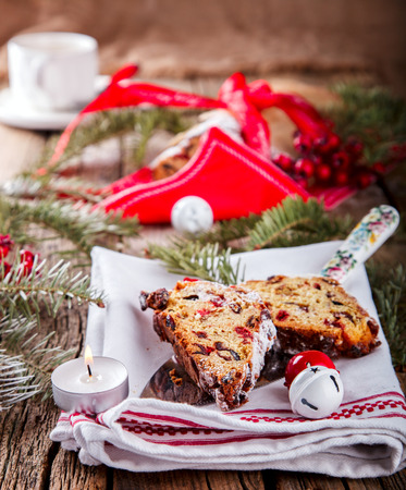 Dresdnen Stollen is a Traditional German Cake with raisins on a light knitted background.Gift for Christmas.Vintage style.Fruit cake for the Holiday. German, European festive dessert. Stock Photo