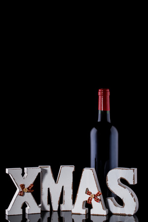 Christmas  Bottle of Red Wine for a Festive Fragrant Traditional Drink Mulled wine Alcohol on the Black Background Decoration Stock Photo