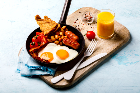 Traditional English Breakfast in the Frying Pan Eggs Heart shape. Valentines Day. Festive Food on the Blue Background.Sausages, Bacon, Beans,Toasts,Coffe and Orange juice