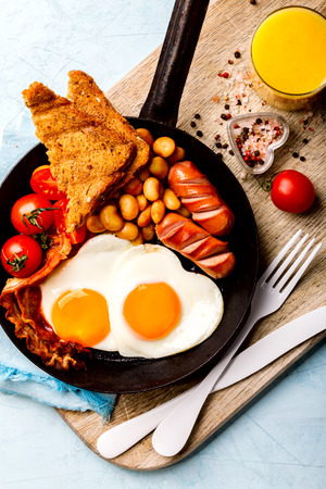 Traditional English Breakfast in the Frying Pan Eggs Heart shape. Stock Photo