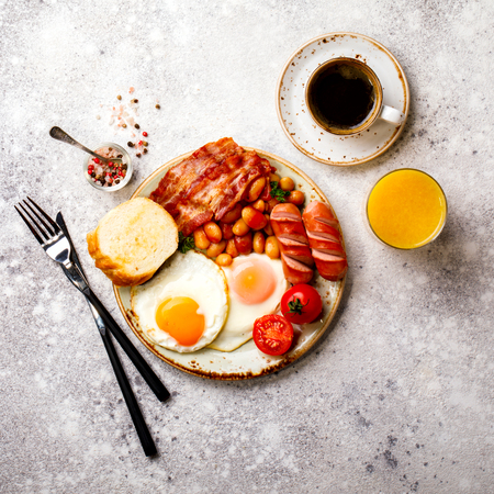 Traditional English Breakfast Food on stone Eggs ,Sausages, Bacon, Beans,Toasts,Coffe and Orange juice Top View