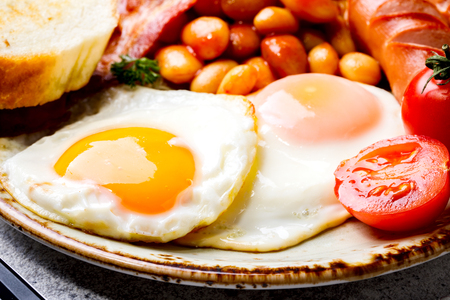 Traditional English Breakfast Food on stone Eggs ,Sausages, Bacon, Beans,Toasts