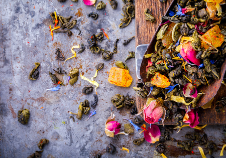 Dry Tea on the basis of Green with fruits and  rose petals, cornflower and calendula on a wooden background Stock Photo