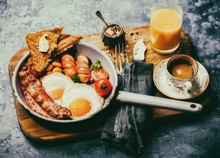 Traditional English Breakfast in the Frying Pan  Food on the Blue Background. Eggs, Sausages, Bacon, Beans,Toasts,Coffe and Orange juice Toned image Vintage style  Stock Photo