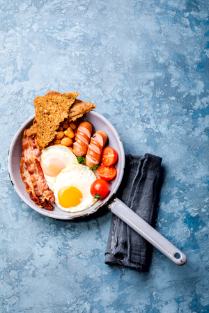 Traditional English Breakfast in the Frying Pan  Food on the Blue Background. Eggs, Sausages, Bacon, Beans,Toasts,Coffe and Orange juice Copy space for Text