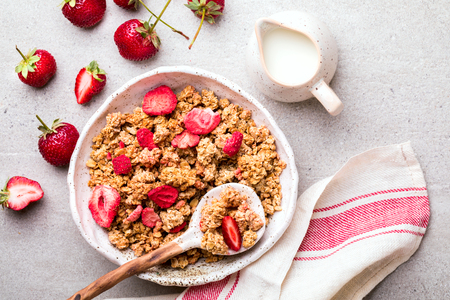 Granola Cereal bar with Strawberries and Milk on the Gray Background. Muesli with  fruit and berries Useful Breakfast. Healthy Food sweet dessert snack. Diet Nutrition Concept. Top View. Vegetarian food.Flat Lay.Copy space for Text.