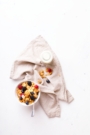 Granola Cereal bar with Strawberries blueberries and Milk on light Background . Muesli Breakfast. Healthy Food sweet dessert snack. Diet Nutrition Concept. Vegetarian food. Flat Lay. Copy space