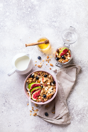 Muesli with Nuts Yogurt and fresh Figs Blueberry on the gray Background.Granola Healthy Breakfast. Sweet food Dessert. Snack  Dry Diet Nutrition Concept.Top View. Flat Lay.Copy space for Text