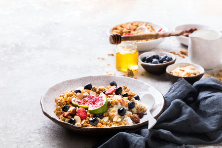 Muesli with Nuts Yogurt and fresh Figs Blueberry on the gray Background.Granola Healthy Breakfast. Sweet food Dessert. Snack  Dry Diet Nutrition Concept.Copy space for Text