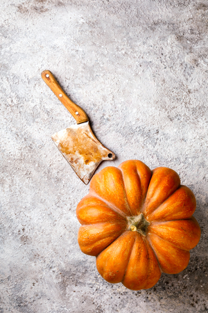 Concept Autumn still life. Pumpkin Fresh on a stone background.Vintage Kitchen Ax for felling Meat on a wooden board.Knife, Ceaver, Cutter with wooden Handle.  Top View. Copy space for Text. Stock Photo